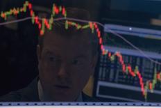 Отражение трейдера, работающего на фондовой бирже в Нью-Йорке, в экране его компьютера. 25 августа 2015 года. Инвесторы бежали в активы развивающихся рынков в течение прошедшей недели, выводя рекордные объемы средств из европейских, американских и японских акций, сообщил в пятницу Bank of America Merrill Lynch (BAML). REUTERS/Brendan McDermid