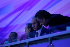 Russian President Vladimir Putin (L) listens to Sports Minister Vitaly Mutko (R) as he watches the ceremony during the opening of the Summer Universiade at the Kazan Arena Stadium in Kazan, Russia, July 6, 2013.  Sputnik/Kremlin/Mikhail Klimentyev/via REUTERS/File Photo