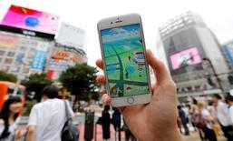 """Un hombre posa con su celular que muestra el juego """"Pokemon Go"""" de Nintendo frente a una calle del distrito de Shibuya en Tokio, Japón, 22 de julio, 2016. El creador del popular juego para móviles Pokemon Go fue recibido como una celebridad el domingo en el último día de la convención anual de cómics de San Diego, donde se refirió a la masiva popularidad y el futuro de la aplicación. REUTERS/Toru Hanai"""