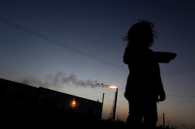 A child stands in front of her house as the Cardon refinery, which belongs...