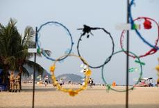 Policemen stand near mock Olympic rings made of recycled plastic on Copacabana Bean in Rio de Janeiro, less than two weeks before the start of the Rio 2016 Olympic Games, July 25, 2016. REUTERS/Kai Pfaffenbach
