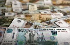 Рублевые купюры. Рубль обновил одномесячные минимумы на торгах четверга в условиях низких нефтяных цен и по мере ухода с рынка экспортеров, которые продажами выручки под уплату налога на прибыль утром и днем сдерживали ослабление российской валюты. REUTERS/Kacper Pempel