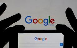Los ingresos de Alphabet, la matriz de Google, se incrementaron un 23,1 por ciento en el segundo trimestre, mejor de lo esperado por el mercado, debido a sólidas ventas de publicidad en dispositivos móviles y de contenido de videos. En la imagen, una mujer sostiene su telefóno inteligente ante la página de inicio de Google. Ilustración realizada el 24 de febrero de 2016. REUTERS/Eric Gaillard