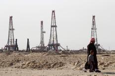 Мужчина с ребенком на нефтяном месторождении Румайла в Басре. 26 января 2016 года. Добыча нефти в странах ОПЕК, вероятно, достигнет максимального объёма за последние годы, говорится в результатах исследования Рейтер, поскольку Ирак наращивает добычу чёрного золота, а Нигерии удаётся экспортировать дополнительные объёмы, несмотря на нападения боевиков на нефтяные объекты. REUTERS/Essam Al-Sudani/File Photo