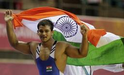 Narsingh Pancham Yadav holds his national flag as he celebrates winning the gold medal in the 74kg men's freestyle wrestling match at the Commonwealth Games in New Delhi October 9, 2010. REUTERS/Krishnendu Halder/Files