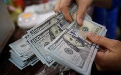 """Банковский служащий пересчитывает доллары в Ханое, Вьетнам. Доллар удерживался вблизи трехнедельных минимумов во вторник после того, как слабые экономические данные из США снизили вероятность скорого повышения ставки Федеральной резервной системой, в то время как """"австралиец"""" на короткое время упал после снижения ключевой ставки ЦБ. REUTERS/Kham"""