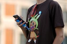 "A young man plays the augmented reality mobile game ""Pokemon Go"" by Nintendo at Puerta del Sol square in Madrid, Spain July 28, 2016. REUTERS/Sergio Perez"