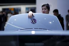 A woman looks a Volkswagen car during a presentation at the 16th Shanghai International Automobile Industry Exhibition in Shanghai, April 21, 2015. REUTERS/Aly Song/File Photo