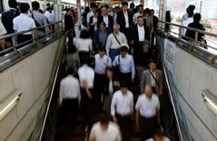 People walk down stairs in a train station in Tokyo's business district September 30, 2014. REUTERS/Yuya Shino