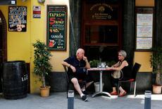 El sector servicios creció en España a un ritmo ligeramente más lento en julio, pese a que hoteles y restaurantes registraron un fuerte aumento de la actividad durante la temporada turística, mientras que la contratación se mantuvo cerca de máximos de ocho años, según un sondeo difundido el miércoles. En la imagen, un pareja sentada en un restaurante de una zona turística de Sevilla, el 5 de julio de 2016. REUTERS/Marcelo del Pozo