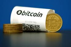 Ilustración fotográfica que muestra una boleta junto a monedas con el logo de Bitcoin, en París, Francia. 27 de mayo de 2015. Cerca de 120.000 unidades de la moneda digital bitcoin valoradas en unos 72 millones de dólares fueron robadas de la plataforma de intercambio Bitfinex en Hong Kong, lo que sacudió a la comunidad global de bitcoins en la segunda mayor brecha de seguridad en el mercado de moneda digital. REUTERS/Benoit Tessier/File Photo