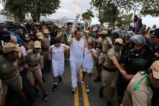 Mayor Eduardo Paes (C) carries the Olympic torch just after it was transported across Guanabara Bay from Niteroi to Rio de Janeiro three days before the official start of the Rio 2016 Olympic Games, in Rio de Janeiro, Brazil,  August 3, 2016.  Beth Santos/Courtesy of Rio de Janeiro City Hall/Handout via REUTERS
