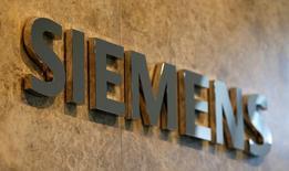 El conglomerado industrial germano Siemens revisó al alza su previsión de beneficios para el ejercicio fiscal por segunda vez este año y elevó el objetivo de ahorro de costes después de que la mayor parte de sus negocios superase las expectativas en el tercer trimestre. En la foto, el logo de Siemens en su nueva sede central en Munich el 14 de junio de 2016.  REUTERS/Michaela Rehle