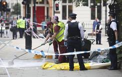 Полицейские и уборщики на месте ночного нападения на площади Рассел-Сквер в Лондоне. 4 августа 2016 года. Один человек погиб и пятеро пострадали, после того как мужчина, вероятно, страдающий душевным расстройством, набросился с ножом на прохожих в центре Лондона. REUTERS/Neil Hall