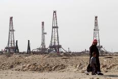Personas caminando cerca del campo petrolero Rumaila, en Basora, Irak. 26 de enero de 2016. La producción de petróleo de Irak subió en julio a su nivel más alto desde enero, en momentos en que la oferta del país se recupera pese a los bajos precios del crudo y un conflicto con militantes del grupo Estado Islámico. REUTERS/Essam Al-Sudani/File Photo