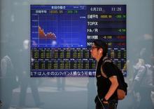 Мужчина проходит мимо экрана с котировками индекса Nikkei в Токио 2 июня 2016 года. Японский индекс Nikkei растерял набранное ранее в течение сессии преимущество и завершил на отрицательной территории торги пятницы и неделю, омрачённую укреплением иены и разочарованием мерами стимулирования центрального банка и правительства.  REUTERS/Issei Kato