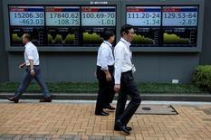 Peatones caminando cerca de unas pantallas que muestras el índice Nikkei de Japón, afuera de una correduría en Tokio. 6 de julio de 2016. El promedio bursátil japonés Nikkei tocó un máximo de una semana el lunes, impulsado por el avance de Wall Street y el retroceso del yen tras el sólido reporte de nóminas no agrícolas de Estados Unidos, publicado el viernes. REUTERS/Issei Kato