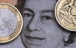 Ilustración fotográfica de una moneda de dos euros junto a una de una libra, sobre un retrato de la Reina Isabel. 16 de marzo de 2016. La libra esterlina caía el martes por quinta sesión consecutiva, después de que un integrante del Banco de Inglaterra dijo que probablemente sea necesario un mayor alivio cuantitativo si empeora el declive económico en Reino Unido. REUTERS/Phil Noble/Illustration/File Photo