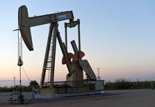 Una unidad de bombeo de crudo funcionando cerca de Guthrie, EEUU, sep 15, 2015. Los futuros del petróleo cayeron un 1 por ciento el martes porque la preocupación por un persistente exceso global de suministros contrarrestó los pronósticos de una caída de los inventarios de crudo en Estados Unidos.   REUTERS/Nick Oxford