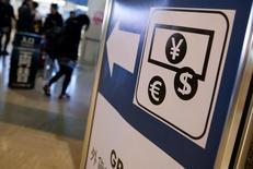 Указатель на пункт обмена валюты в аэропорту Токио. Доллар США упал к иене в среду поскольку ставки на иену выросли из-за падения японских акций, в то время как погоня за выгодными сделками помогла фунту вырасти с месячного минимума. REUTERS/Yuya Shino/File Photo