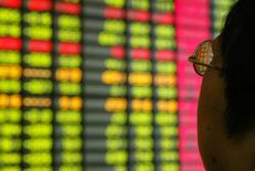 Un inversor chino mira un monitor que muestra información bursátil en una correduría en Shanghái. 12 de noviembre de 2003. Las acciones chinas cayeron el jueves, revirtiendo ganancias previas, debido a que fuertes correcciones de los títulos ligados a materias primas y pequeños inversores presionaron a la baja a los principales índices, pese al avance de los papeles del sector financiero. REUTERS/Claro Cortes IV/File Photo