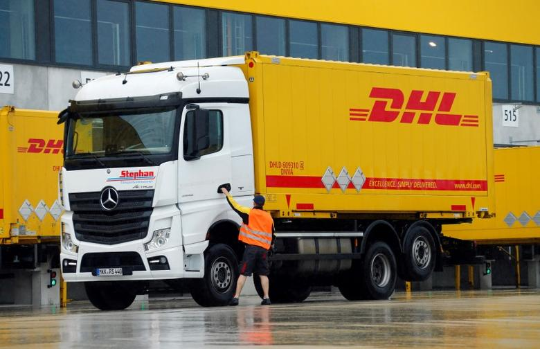 A worker opens a truck at a distribution centre of German postal and logistics group Deutsche Post DHL in Obertshausen, Germany June 15, 2016. REUTERS/Ralph Orlowski