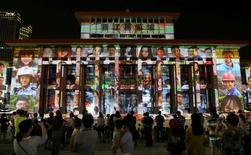 Personas mirando un show de luces que anuncia la realización de la cumbre G20 en el próximo mes, en Hangzhou. 5 de agosto de 2016. China espera que la cumbre del G20 que presidirá el próximo mes se enfoque en impulsar el crecimiento económico y otros aspectos financieros y no en disputas como las del Mar de China Meridional, dijeron altos funcionarios el lunes. REUTERS/Stringer