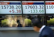 Un hombre camina frente a una pantalla que muestra información bursátil, afuera de una correduría en Tokio, Japón. 6 de abril de 2016. Las bolsas de Asia se alejaban el miércoles desde unos máximos en un año y el dólar se fortalecía luego de que un influyente funcionario de la Reserva Federal de Estados Unidos dijo que las tasas de interés podrían subir tan pronto como en septiembre. REUTERS/Issei Kato