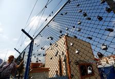 """Демонстрант у ограждения тюрьмы """"Метрис"""" в Стамбуле 24 июня 2016 года. Турция даст свободу примерно 38 тысячам заключенных, объявив в среду о реформе пенитенциарной системы, после того как десятки тысяч арестованных по подозрению в причастности к июльской попытке переворота переполнили тюрьмы. REUTERS/Murad Sezer"""