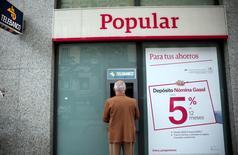 Banco Popular ha comprado acciones propias equivalentes a un uno por ciento de su capital entre el 22 de julio y el 16 de agosto, según información que figura en los registros del  regulador bursátil. En esta imagen de archivo, un hombre utiliza un cajero de Popular en Madrid, el 29 de abril de 2016.  REUTERS/Andrea Comas