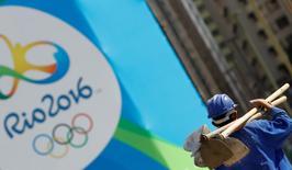 Un trabajador de la construcción camina cerca de un logo de los Juegos Olímpicos de Río 2016, en Río de Janeiro. 27 de julio de 2016.  La estatal brasileña Petrobras podría adquirir los derechos de comercialización de los Juegos Paralímpicos que se celebrarán en septiembre en Río de Janeiro, dijo a Reuters una fuente involucrada en las negociaciones.        REUTERS/Kai Pfaffenbach