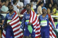 Mike Rodgers, Justin Gatlin and Tyson Gay react after being disqualified along with Trinidad and Tobago. TV pictures showed U.S. runner Trayvon Bromell stepping into Usain Bolt's lane in the run to the line. REUTERS/Lucy Nicholson
