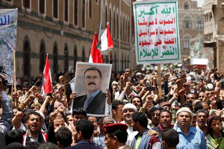 People hold a poster of Yemen's former president Ali Abdullah Saleh as they demonstrate outside a parliament session held for the first time since a civil war began almost two years ago, in Sanaa, Yemen August 13, 2016. T REUTERS/Khaled Abdullah