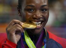 2016 Rio Olympics - Boxing - Victory Ceremony - Women's Middle (75kg) Victory Ceremony - Riocentro - Pavilion 6 - Rio de Janeiro, Brazil - 21/08/2016. Gold medallist Claressa Shields (USA) of USA bites her medal from Rio 2016.  REUTERS/Peter Cziborra