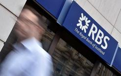 A man walks past a branch of The Royal Bank of Scotland (RBS) in central London, Britain August 27, 2014. REUTERS/Toby Melville/Files