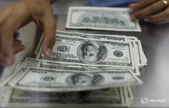"""Женщина пересчитывает долларовые купюры в пункте обмена валюты в Янгоне 23 мая 2013 года. Доллар снизился во вторник, поскольку инвесторы переключили внимание с """"ястребиных"""" комментариев представителей Федеральной резервной системы о ключевой ставке на выступление главы регулятора Джанет Йеллен, которое должно состояться в пятницу. REUTERS/Soe Zeya Tun"""