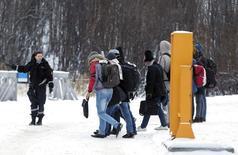 Пересекшие границу со стороны России мигранты получают указания сотрудницы норвежской полиции на погранпункте Сторског 16 ноября 2016 года. Норвегия построит стальной забор на арктическом погранпункте из-за большого наплыва мигрантов, бегущих в Скандинавию через Россию. REUTERS/Cornelius Poppe/NTB Scanpix