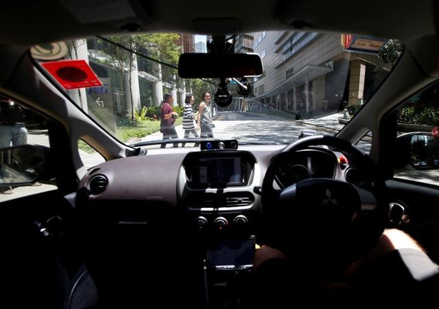 Os pedestres atravessar a estrada como um táxi auto-condução nuTonomy sofre seu julgamento público em Singapura 25 de agosto de 2016. REUTERS / Edgar Su