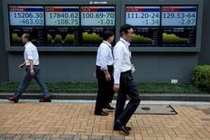 Peatones caminando frente a pantallas que muestran información bursátil, afuera de una correduría en Tokio, Japón. 6 de julio de 2016. Las bolsas de Asia subían el jueves y el dólar se afirmaba frente a las monedas de la región antes de un discurso de la presidenta de la Reserva Federal de Estados Unidos, Janet Yellen, en una conferencia de jefes de bancos centrales. REUTERS/Issei Kato