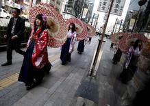 Los precios subyacentes al consumidor de Japón cayeron por quinto mes consecutivo en julio y registraron su mayor declive interanual en más de tres años, después de que más empresas se abstuvieran de subir los precios debido a la debilidad del consumo. En la imagen de archivo, mujeres en kimono caminan por una calle con sombrillas en Tokio. REUTERS/Yuya Shino/File Photo