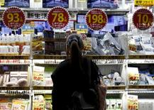 Женщина изучает товар в магазине в торговом районе Токио. Снижение базовых потребительских цен в Японии в июле в годовом исчислении оказалось сильнейшим за более чем три года, поскольку компании отложили повышение цен на фоне слабого спроса, вынуждая Банк Японии расширить и без того масштабную программу стимулирования экономики.  REUTERS/Yuya Shino