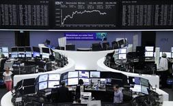 Traders work at their desks in front of the German share price index, DAX board, at the stock exchange in Frankfurt, Germany, August 24, 2016. REUTERS/Staff/Remote