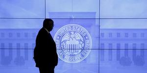 A guard walks in front of a Federal Reserve image before press conference...