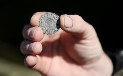 A mudlark shows a Henry VII coin that he excavated from the River Thames in London, Britain May 23, 2016. REUTERS/Neil Hall