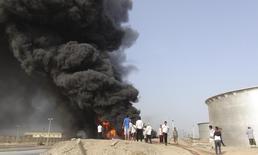 Люди у загоревшихся нефтяных хранилищ на НПЗ в Адене, Йемен, 27 июня 2015 года. REUTERS/Stringer