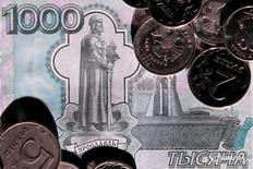 Рублевые монеты и купюра 7 июня 2016 года. Волатильность курса рубля во втором квартале 2016 года продолжила снижаться вслед за амплитудой колебаний цен на нефть, и в третьем квартале 2016 года может сохраниться на сложившемся уровне, говорится в последнем выпуске финансового обозрения регулятора. REUTERS/Maxim Zmeyev/Illustration