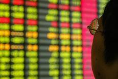 Un inversor chino mira un monitor que muestra información bursátil en una correduría en Shanghái. 12 de noviembre de 2003. Las acciones chinas cerraron estable el lunes, luego de que los avances de los valores industriales contrarrestaron el descenso en el sector bancario. REUTERS/Claro Cortes IV/File Photo