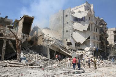 Men inspect a damaged site after double airstrikes on the rebel held Bab...