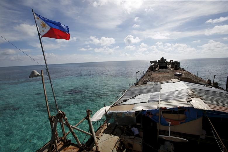 A Philippine flag flutters from BRP Sierra Madre, a dilapidated Philippine Navy ship that has been aground since 1999 and became a Philippine military detachment on the disputed Second Thomas Shoal, part of the Spratly Islands, in the South China Sea March 29, 2014. Picture taken March 29, 2014.  REUTERS/Erik De Castro