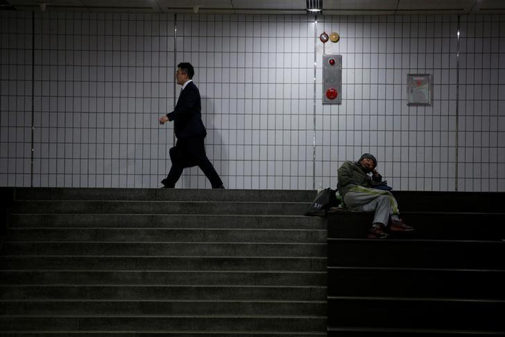 A man walks past a homeless man at an underground shopping district in Seoul, South Korea, July 12, 2016. REUTERS/Kim Hong-Ji